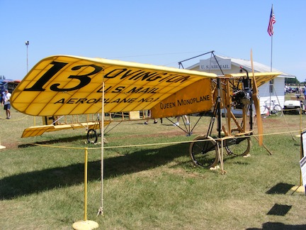 The yellow monoplane is sitting on grass.