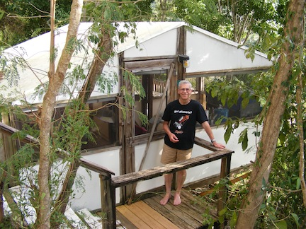 Al, wearing a Kepler             T-shirt and shorts, stands in front of the door to the             canvas and screen cabin. Trees surround the scene.