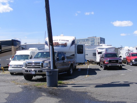 Our Ford F-250 truck and Copper Canyon 5th wheel trailer                 are parked behind a light pole in the Liberty Harbor RV Park.                 The ground is covered with asphalt and gravel. Campers are                 very close together side-by-side and back to back. The                sky is blue with a few puffy white clouds.