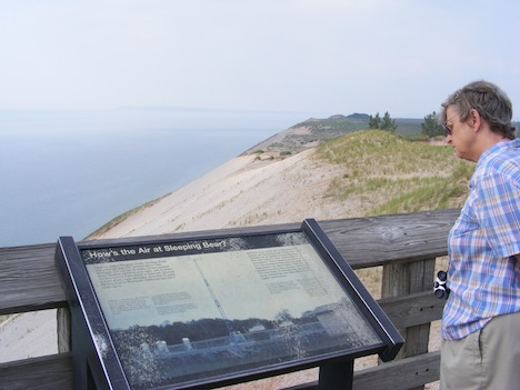 Gail reads a plaque on a viewing                 platform. A steep sand and                 rock slope stretching from the top of the                 dunes down to the lake shore can be seen                 behind the plaque