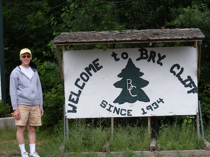 Al stands alongside the sign that                says we welcome you to Bay Cliff, established 1934