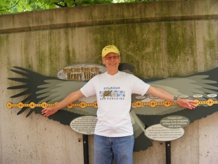 Al stretches his arms in front of a                representation of the different wingspans.                His arm reach matches the wingspan of a                 vulture.