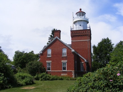 The photo was taken from the side of the                lighthouse. The square tower is attached                to the front of the residence. Both are                painted red.