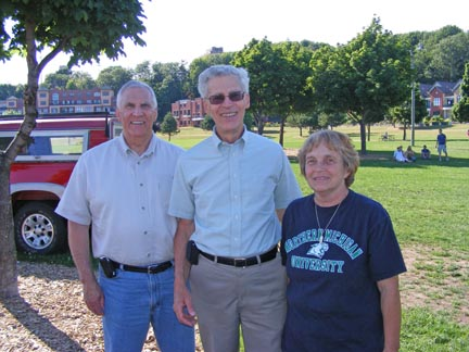Carl, Al and Ruth Ann stand in the shade of a                 tree. A grassy field is behind them.
