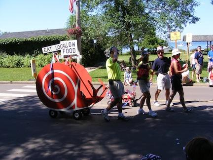 A red-colored cardboard snail on a wagon pulled                by some walkers has signs for Eat Local and Slow Food