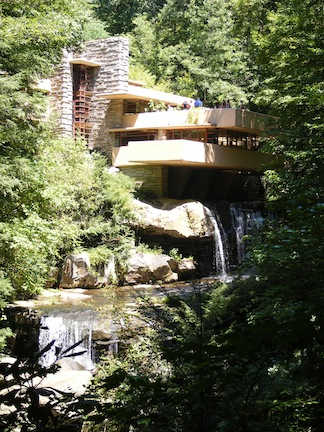 Cantilevered terraces jut out over                the two small falls below. Tree branches                frame the image.
