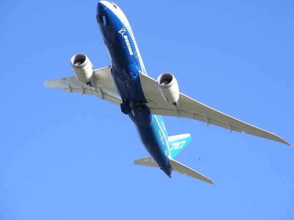 The plane is seen from below as it passes overhead.                The nose is at the top of the image. The body of the                 plane is painted white, dark blue and light blue.
