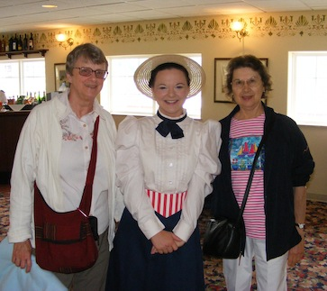 The picture is taken in the waiting room on                the second level of the showboat. Gail and Julie                flank the actress who is wearing a straw hat,                white blouse, black skirt, peppermint-striped                belt, and a black bow tie.