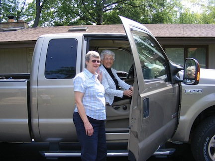 92-year-old Millie sits in the                    passenger seat while Gail stands                    alongside the open door
