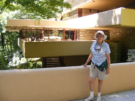 Gail stands on the walkway to                 the entrance to the house. The tan-colored                cantilevered terraces are behind her.
