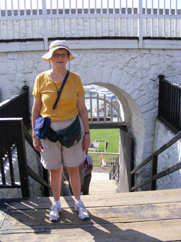 Gail stands at the southern gate through                the stone wall of the fort. A little of                 Marquette Park is visible 150 feet below.