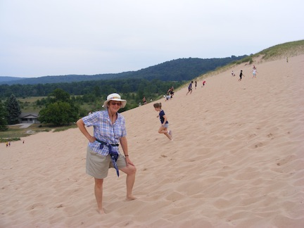 Gail is standing with one foot up the                 slope  of fine sand. Behind her a young girl                is running down the hill.