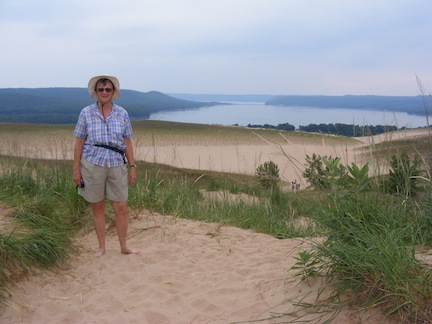 Gail faces the camera. In the distance behind                her is Glen Lake. There is sand at the top, but                 surrounded by dune vegetation. A wide bench of sand                is behind and below her.