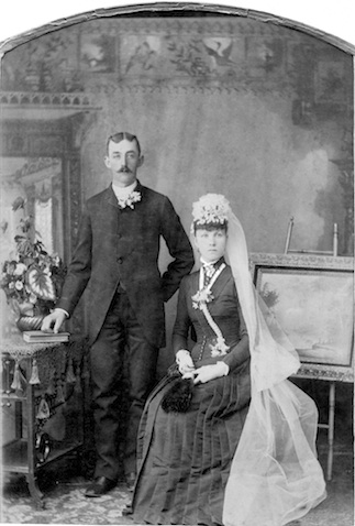 Fred Henjes is standing to the             left of Ella, who is sitting, possibily on a stool. He is             wearing a dark suit and she is wearing a long, dark              dress. Her hat has a long, white veil attached.              There is a table and a painting on an easel in the              photograph.