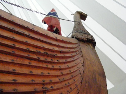 Seen from below, the prow of the replic                  Viking ship rises high to the animal figure head.                  The overlapping of the boards forming the                  body of the boat is accentuated.
