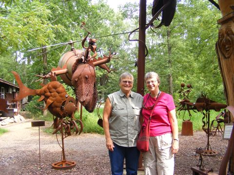 Linda and Gail are standing with the Attack Dragon                in the background. The Dragon has its head lowered                and has a helicopter-like rotor spinning on its back.                Near the right side of the photo is a deep-sea looking                creature. All the creatures are rusty. Trees are in the                background.