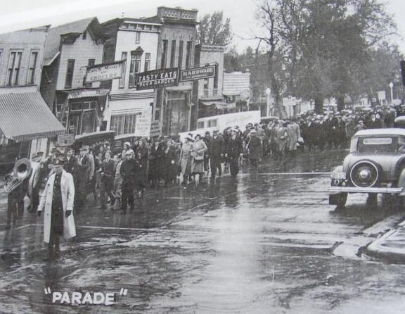 A black and white photo showing a parade in front of                the west side of Freeman Street on October 25, 1936. People                are wearing overcoats and the street looks wet as if it                is raining or has rained recently.