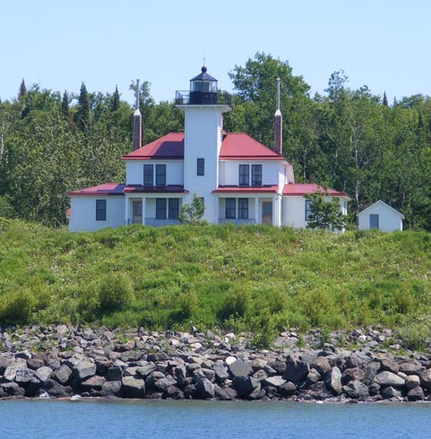 The photo was taken from a boat on Lake                   Superior. The square tower for the light                   is build into the residence for the                    keeper and his assistant. The walls                   are white and the roof of the house is                   red.