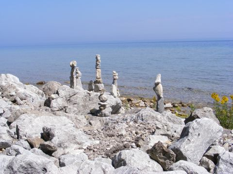 Six or Seven piles of rocks on the rocky shore                of Lake Huron. The blue water and blue sky.