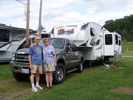 Al and Gail standing in front of their F-250 tow                truck and Copper Canyon 5th wheel trailer, on a flat                field at the Fox Den Campgound in New Stanton, PA.